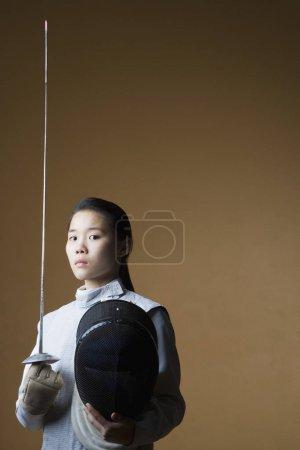 Photo pour Portrait d'une femme portant une épée et un masque d'escrime - image libre de droit