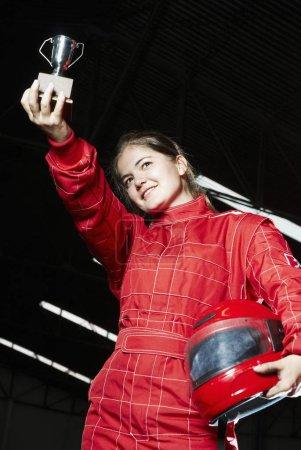 Photo pour Vue à faible angle d'un coureur de go-cart féminin tenant un trophée et souriant - image libre de droit