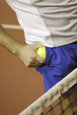 Photo pour Vue en plein milieu d'un homme sortant une balle de tennis de sa poche - image libre de droit