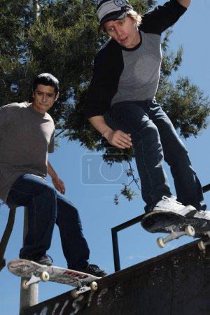 Photo pour Vue à faible angle de deux jeunes hommes planche à roulettes - image libre de droit