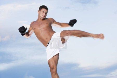 Photo pour Vue à faible angle d'un jeune homme qui donne un coup de pied - image libre de droit