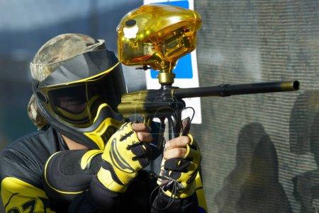 Photo pour Gros plan d'un homme d'âge moyen visant avec un pistolet à balles de peinture - image libre de droit