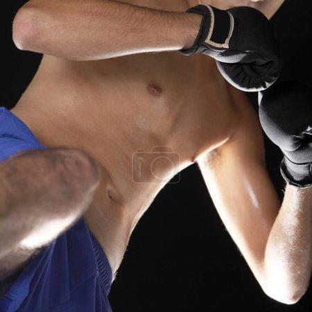 Photo pour Vue à angle bas d'un jeune homme portant des gants de boxe - image libre de droit