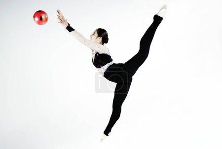 Photo pour Profil latéral d'une gymnaste s'entraînant avec un ballon - image libre de droit
