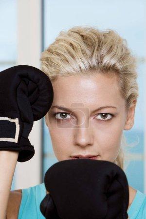Photo pour Gros plan sur une jeune femme portant des gants de boxe - image libre de droit