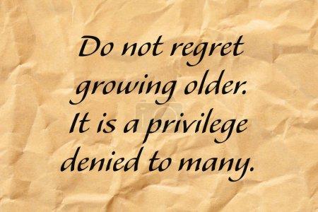 Foto de No se arrepienta de envejecer. Es un privilegio que se niega a muchos. Cita de edad positiva escrita en papel marrón triturado. - Imagen libre de derechos