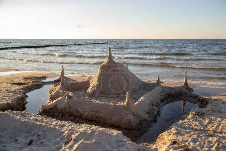 Photo pour Un château de sable sur la plage le soir au coucher du soleil - image libre de droit