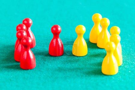 Foto de Escena conceptual - pocos peones rojos con líder delante de varios peones amarillos con líder en la mesa de bajos verdes. - Imagen libre de derechos