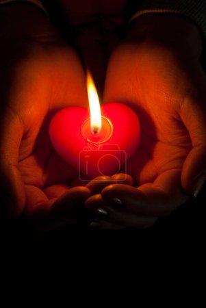 Photo pour Les mains humaines retiennent la bougie brûlante formée de coeur sur le fond foncé - image libre de droit