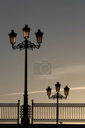 Photo pour Old street lamps and railings on a bridge in Chiclana de La Frontera, Andalusia, Spain. The lamps are not yet lit, but backlit by the dawning sun. - image libre de droit