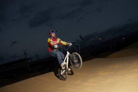 Photo pour Jeune homme faisant un coup de pied sur une bicyclette - image libre de droit