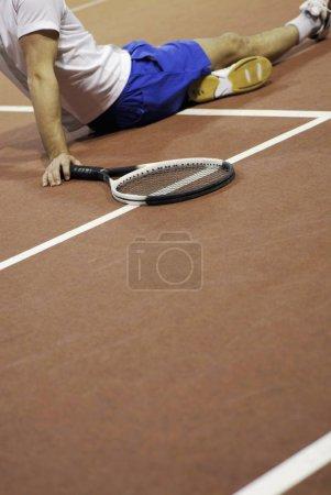 Photo pour Profil latéral d'un homme assis sur un court de tennis - image libre de droit