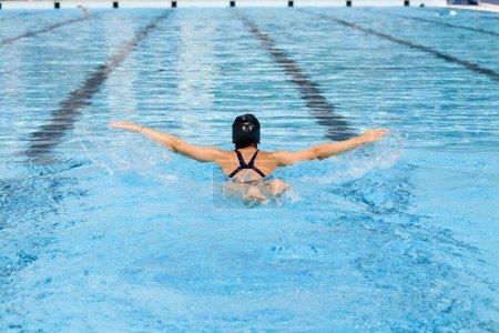 Photo pour Vue arrière d'une jeune femme nageant dans une piscine - image libre de droit