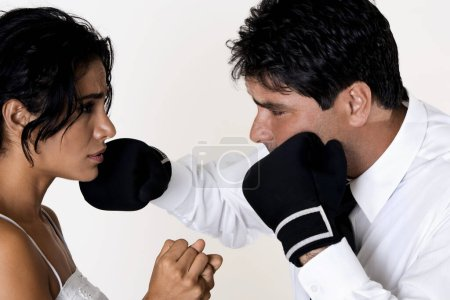 Photo pour Profil latéral d'un homme d'âge moyen donnant des coups de poing à une jeune femme - image libre de droit