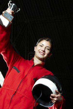 Photo pour Portrait d'un coureur de voitures tenant un trophée la main relevée et souriante - image libre de droit