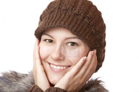 Beautiful woman with wool hat laughs with hands on cheeks
