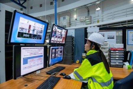 Photo pour Dans la grande usine, une ingénieure en informatique travaille sur un ordinateur personnel - image libre de droit