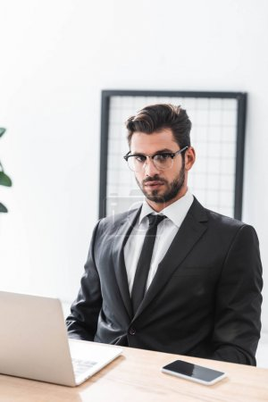 Handsome businessman in eyeglasses looking at camera at workplace