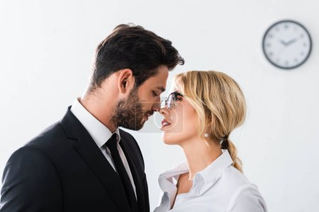 Photo for Side view of business couple looking at each other while flirting in office - Royalty Free Image