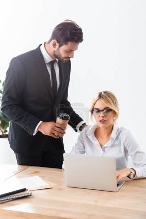 Businessman with coffee looking at colleague working with laptop