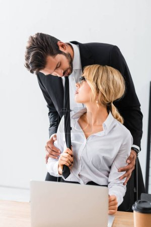 Photo for Sensual businesswoman flirting with colleague by workplace - Royalty Free Image