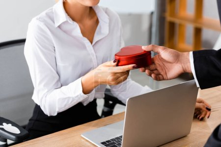 Photo pour Vue recadrée de l'homme d'affaires donnant boîte cadeau à la femme en fonction - image libre de droit
