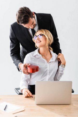 Businessman giving gift box to smiling colleague in office