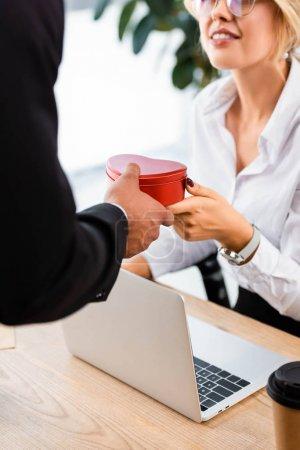 Photo pour Concentration sélective de l'homme d'affaires faisant un cadeau à un collègue souriant en poste - image libre de droit