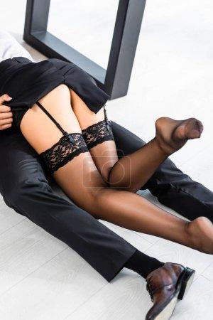 Photo pour Vue recadrée de femme sexy en bas couché sur homme d'affaires sur le sol dans le bureau - image libre de droit