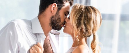 Photo for Business couple kissing while flirting in office, panoramic shot - Royalty Free Image