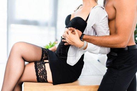 Photo pour Vue recadrée d'un homme torse nu embrassant une femme d'affaires sexy sur une table de bureau - image libre de droit