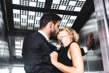 Photo for Businessman kissing colleague in office elevator - Royalty Free Image