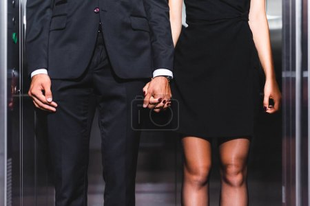 Photo for Cropped view of business couple holding hands in office elevator - Royalty Free Image