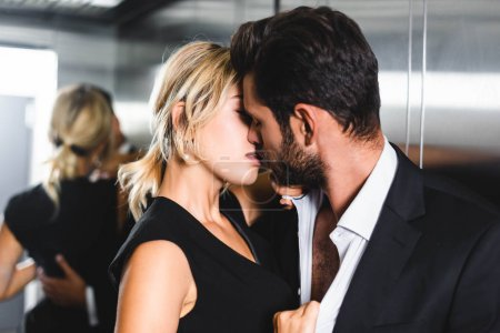 Photo for Businesswoman kissing colleague in office elevator - Royalty Free Image
