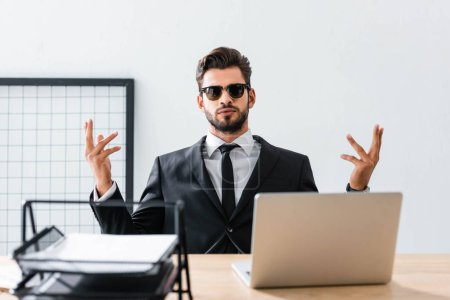 Photo for Handsome businessman in sunglasses gesturing at office table - Royalty Free Image