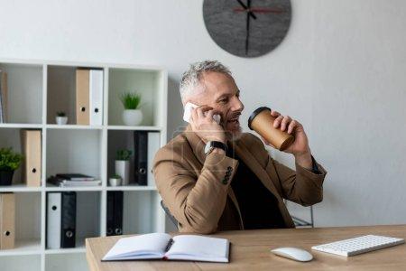 gutaussehender Geschäftsmann, der mit dem Smartphone spricht und im Büro Kaffee trinkt