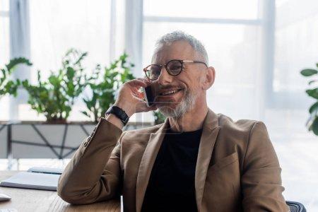 fröhlicher Geschäftsmann mit Brille, der im Büro auf dem Smartphone spricht
