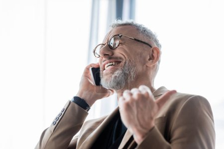 Photo pour Foyer sélectif de l'homme d'affaires heureux et barbu parler sur smartphone et montrant pouce vers le haut - image libre de droit