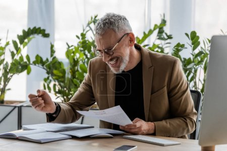 cheerful businessman looking at document near smartphone with blank screen in office