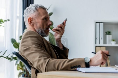 Photo for Side view of bearded businessman recording voice message while holding smartphone - Royalty Free Image