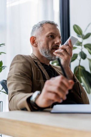 Photo for Selective focus of bearded businessman recording voice message while holding smartphone - Royalty Free Image