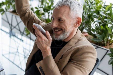 Photo pour Homme d'affaires joyeux enregistrement message vocal près des plantes vertes dans le bureau - image libre de droit