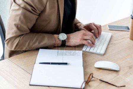 Photo pour Vue recadrée de l'homme d'affaires tapant sur le clavier de l'ordinateur près de portable, stylo, souris d'ordinateur et smartphone avec écran vide - image libre de droit