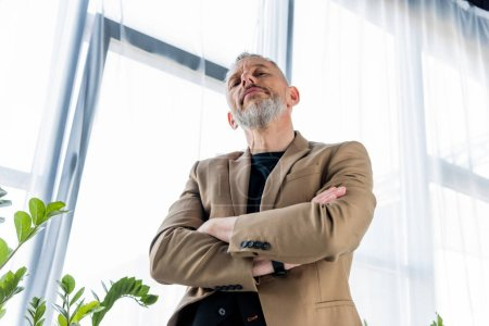 Photo for Low angle view of bearded businessman standing with crossed arms - Royalty Free Image