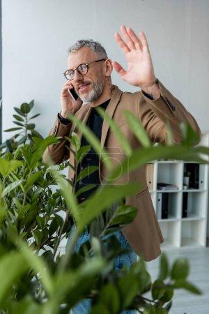 Photo pour Foyer sélectif de l'homme d'affaires heureux agitant la main tout en parlant sur smartphone près des plantes - image libre de droit