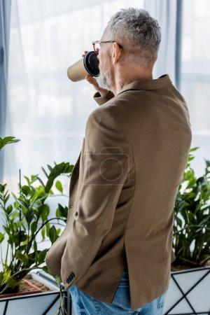 Photo pour Vue arrière de l'homme d'affaires buvant du café pour aller près des plantes - image libre de droit