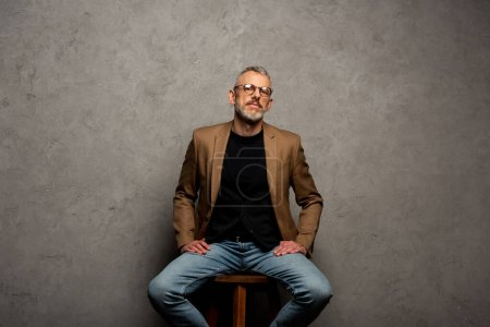 Photo for Bearded businessman in glasses looking at camera and sitting on grey - Royalty Free Image
