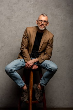 Photo for Bearded businessman in glasses looking at camera and sitting on stool on grey - Royalty Free Image