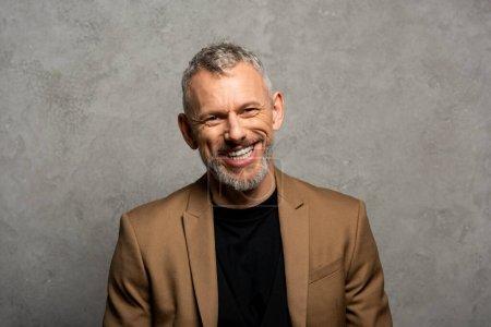 cheerful businessman in blazer looking at camera on grey