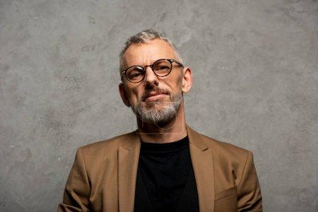 Photo pour Bel homme d'affaires en lunettes regardant la caméra sur gris - image libre de droit
